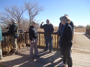 Tom explains to fellow birdwatchers about the daily migration of the cranes from the cornfield--their feeding place--to Whitewater Draw--their loafing area.